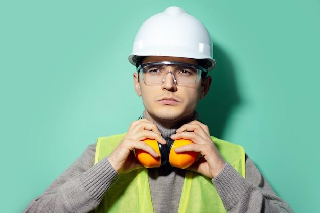 若いビルダーの男、エンジニア、首に彼の建設用ヘッドフォンに触れ、アクアメンテカラーの壁に安全ヘルメットと眼鏡をかけています。