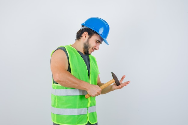 Young builder man hitting hammer on palm in workwear uniform and looking joyful , front view.