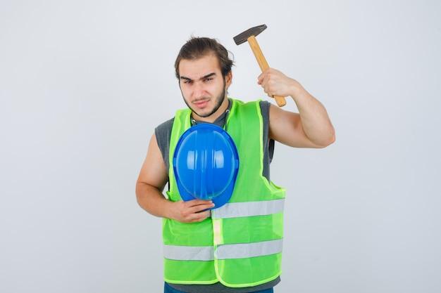 젊은 작성기 남자 작업복 유니폼에 망치와 헬멧을 들고 심각한, 전면보기를 찾고.
