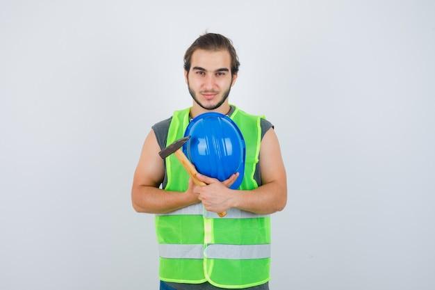 Uomo del giovane costruttore che tiene martello e casco sul petto in uniforme da lavoro e che sembra soddisfatto. vista frontale.