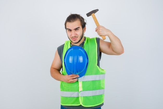 Young builder man holding hammer and helmet in workwear uniform and looking serious , front view.