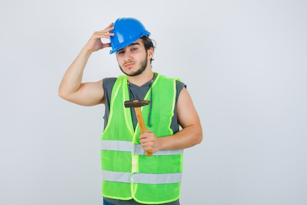 Young builder man holding hammer while keeping hand on head in workwear uniform and looking self-confident , front view.