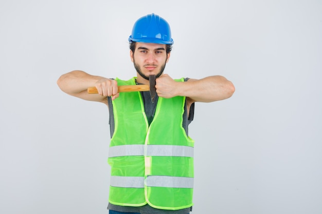 Young builder man holding hammer while showing clenched fist in workwear uniform and looking confident. front view.