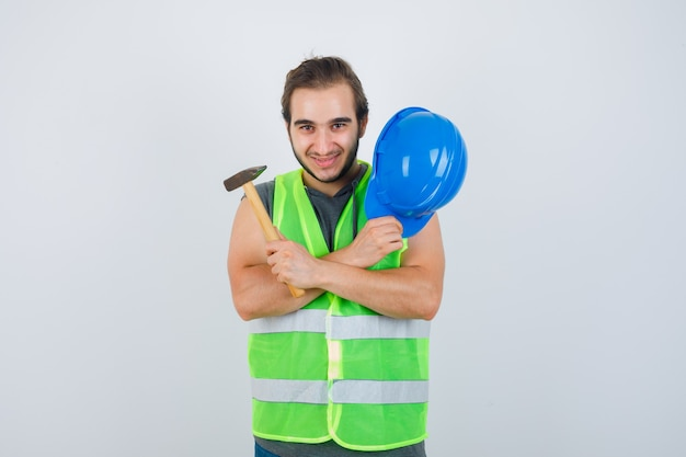Young builder man holding helmet and hammer while crossing arms on chest in workwear uniform and looking joyful. front view.