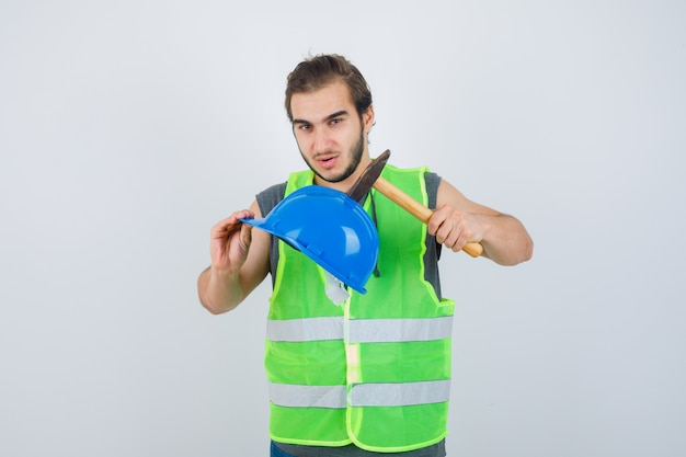 Young builder man holding helmet and hammer in workwear uniform and looking confident. front view.