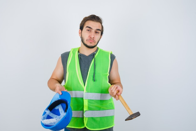 Young builder man holding helmet and hammer in workwear uniform and looking indicisive. front view.