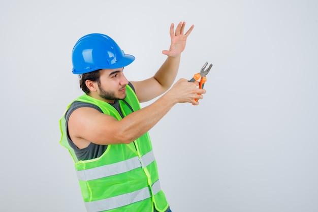 作業服の制服を着て手のひらを上げ、自信を持って見ながらペンチを保持している若いビルダーの男。正面図。