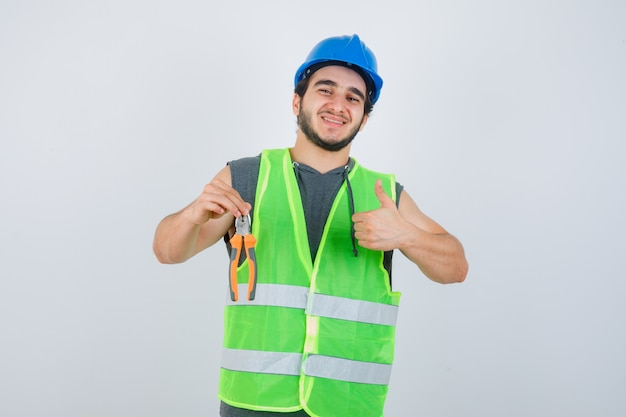 Giovane uomo del costruttore che tiene le pinze mentre mostra il pollice in su in uniforme da lavoro e sembra allegro. vista frontale.