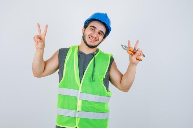 Uomo del giovane costruttore che tiene le pinze mentre mostra il segno di vittoria in uniforme da lavoro e sembra gioioso. vista frontale.