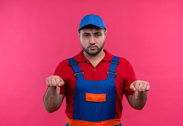 建設ユニフォームと眉をひそめている顔で指を下に向けてキャップを指している若いビルダーの男