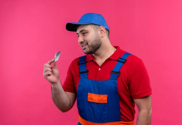 建設の制服を着た若いビルダーの男と笑顔を脇に見ているクレジットカードを示すキャップ