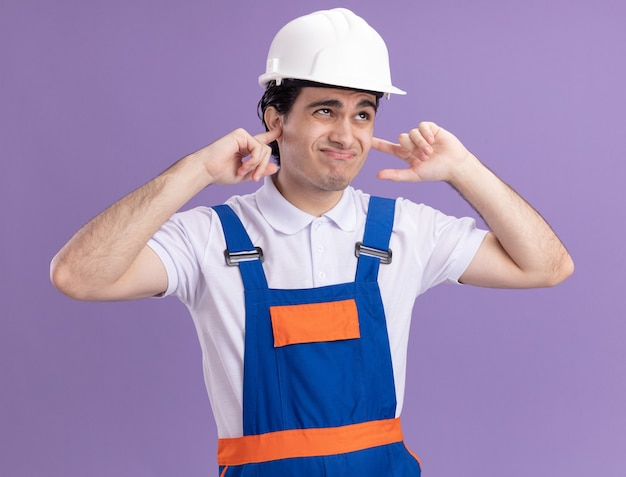 보라색 벽 위에 서있는 성가신 표정으로 손가락으로 귀를 닫는 건설 유니폼 및 안전 헬멧에 젊은 작성기 남자