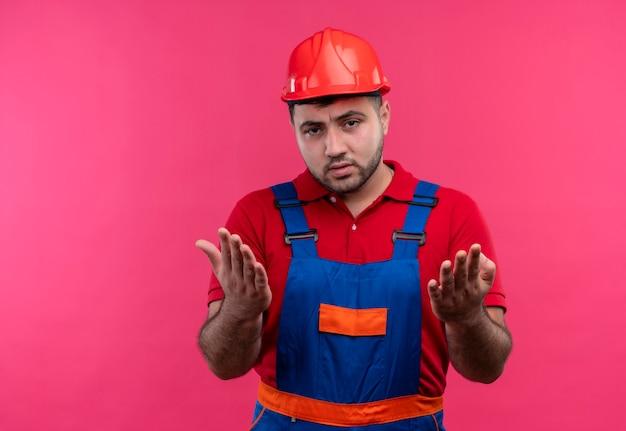 Молодой строитель в строительной форме и защитном шлеме недоволен спорить, жестикулируя руками