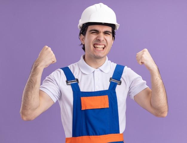 Молодой строитель в строительной форме и защитном шлеме счастлив и взволнован, сжимая кулаки, радуясь своему успеху, стоя над фиолетовой стеной