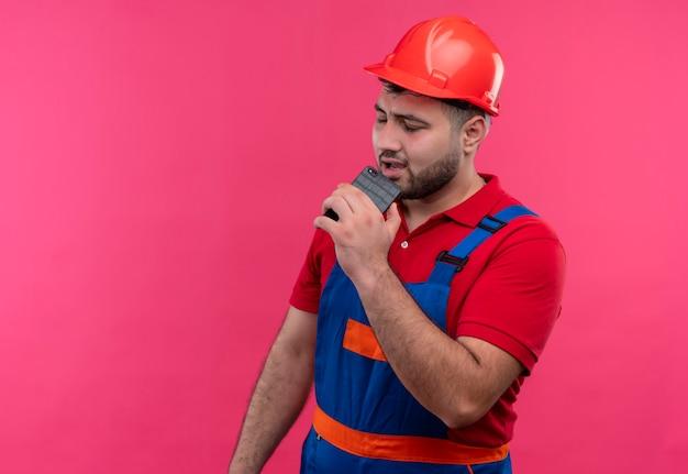 Молодой строитель в строительной форме и защитном шлеме держит смартфон, используя его как микрофонное пение