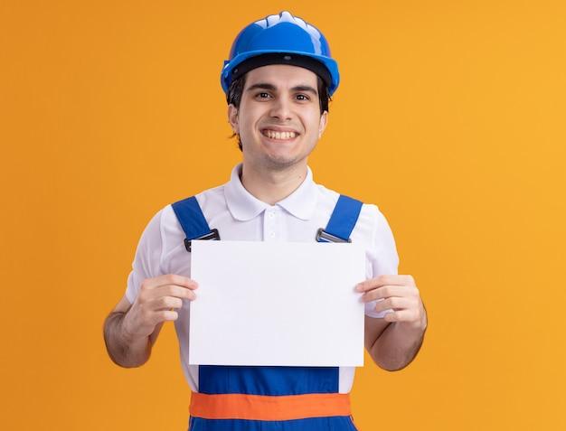 건설 유니폼 및 안전 헬멧에 젊은 작성기 남자 오렌지 벽 위에 유쾌하게 서 웃 고 앞을보고 빈 페이지를 들고