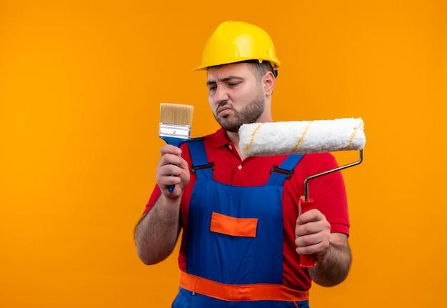 Молодой строитель в строительной форме и защитном шлеме, держа кисть и малярный валик, смотрит на кисть со скептическим выражением лица