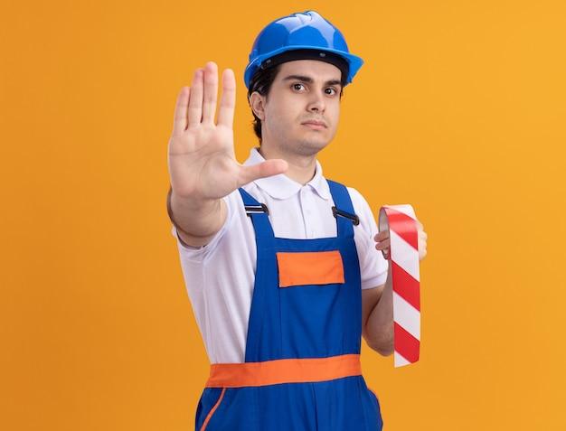 Молодой строитель в строительной форме и защитном шлеме, держащий ленту с предостережением, глядя на фронт, делая стоп-жест рукой, стоящей над оранжевой стеной