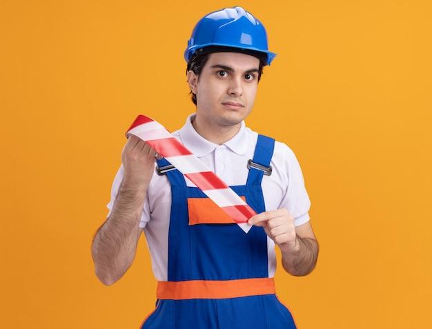 オレンジ色の壁の上に立っている真剣な自信を持って表情で正面を見て注意テープを保持している建設制服と安全ヘルメットの若いビルダー男