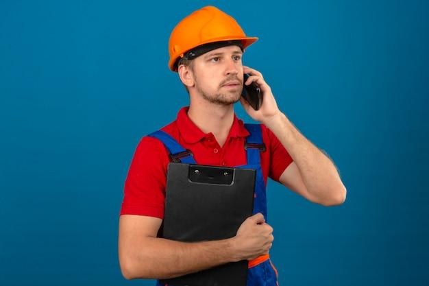 建設制服と安全ヘルメットクリップボードを押しながら青い分離壁を越えて携帯電話で話している若いビルダー男
