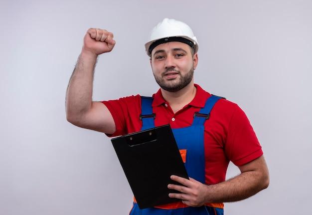 Молодой строитель человек в строительной форме и защитном шлеме, держащий сжимающий кулак с буфером обмена, счастлив и улыбается
