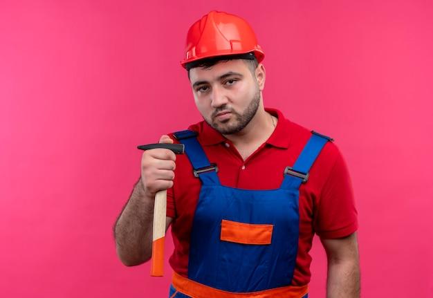 自信を持って見える手にハンマーを保持している建設制服と安全ヘルメットの若いビルダー男