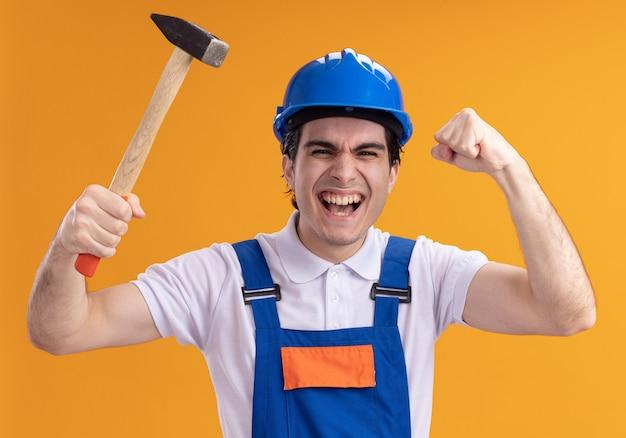 オレンジ色の壁の上に立って幸せで興奮した握りこぶしを正面から見てハンマーを保持している建設制服と安全ヘルメットの若いビルダー男
