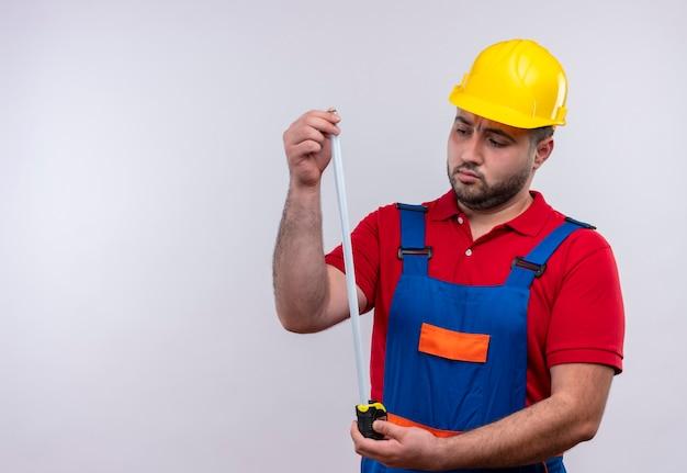 Молодой строитель в строительной форме и защитном шлеме, держащий рулетку, смотрит на нее с серьезным лицом