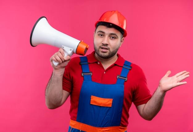 건설 유니폼과 안전 헬멧에 젊은 작성기 남자는 측면에 팔을 확산 혼란 찾고 확성기를 들고