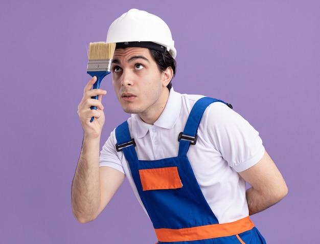 Молодой строитель в строительной форме и защитном шлеме держит кисть, заинтригованно смотрит на нее, стоя над фиолетовой стеной