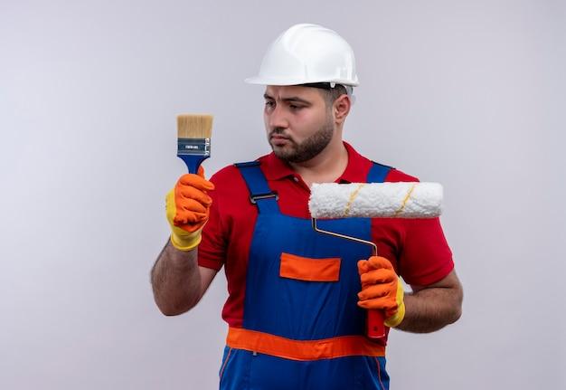 Молодой строитель в строительной форме и защитном шлеме, держащий валик и кисть, смотрит на кисть со скептическим выражением лица