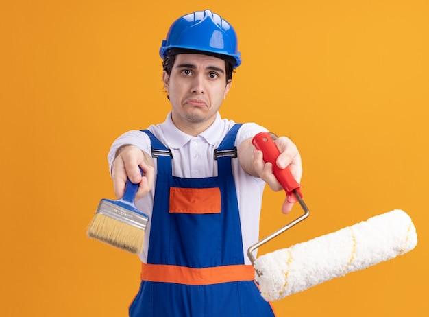 オレンジ色の壁の上に立っている悲しい表情でペイントローラーとブラシを保持している建設制服と安全ヘルメットの若いビルダー男