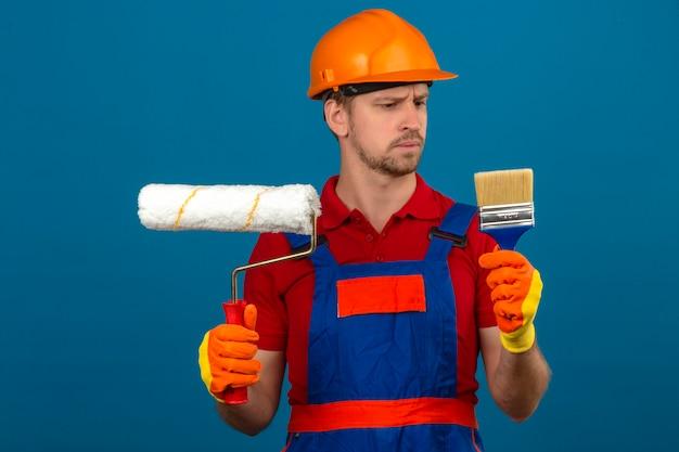 Молодой строитель человек в строительной форме и защитный шлем, держа валик и кисть, глядя на него с скептическим выражением лица на изолированной синей стене