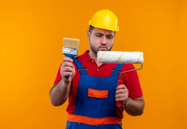 Молодой строитель в строительной форме и защитном шлеме держит малярный валик и кисть, глядя на малярный валик со скептическим выражением лица
