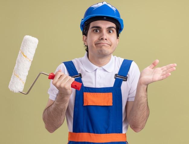 Молодой строитель в строительной форме и защитном шлеме, держащий валик с краской, глядя на перед в замешательстве, пожимая плечами, стоя над зеленой стеной