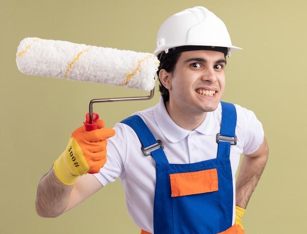Молодой строитель в строительной форме и защитном шлеме, держащий валик с краской, глядя на фронт, счастливым и веселым улыбающимся лицом, стоящим над зеленой стеной