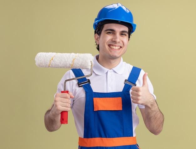 Молодой строитель в строительной форме и защитном шлеме, держащий валик с краской, смотрит на фронт счастливым и позитивным, показывает палец вверх, стоя над зеленой стеной