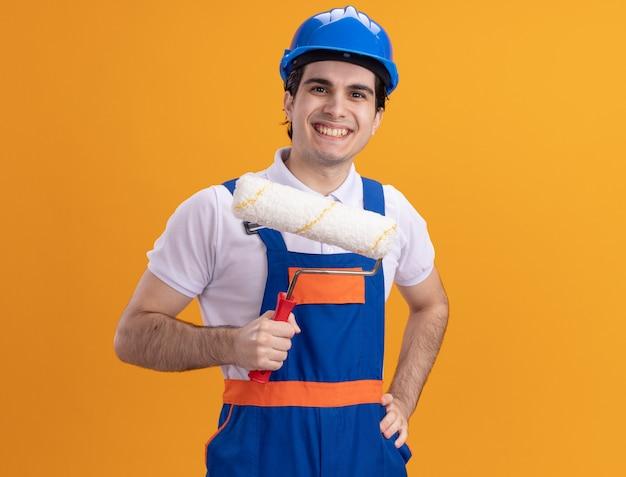 オレンジ色の壁の上に立っている顔に笑顔で正面を見てペイントローラーを保持している建設制服と安全ヘルメットの若いビルダー男