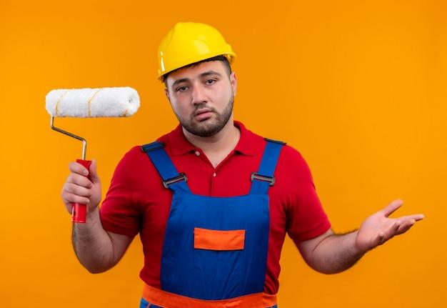 Молодой строитель в строительной форме и защитном шлеме держит валик с краской в замешательстве и разводит руками в стороны