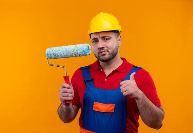 Молодой строитель в строительной форме и защитном шлеме, держащий валик с краской, показывает палец вверх