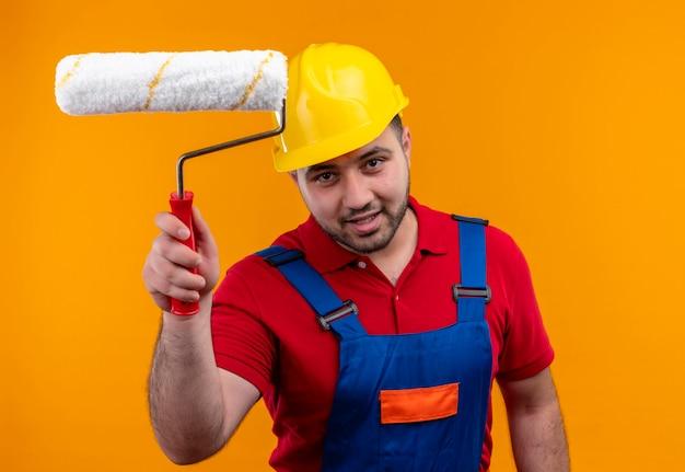 Молодой строитель в строительной форме и защитном шлеме, уверенно улыбаясь, держит валик с краской
