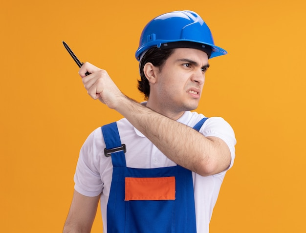 オレンジ色の壁の上に立っている怒っている顔で脇を見てペンを保持している建設制服と安全ヘルメットの若いビルダー男