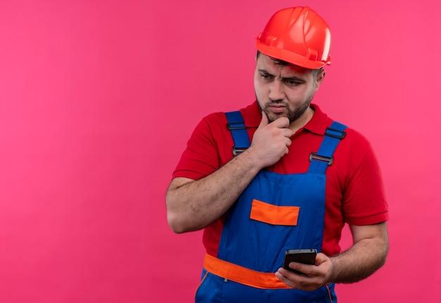 物思いにふける表情で脇を見てスマートフォンを保持している建設制服と安全ヘルメットの若いビルダー男
