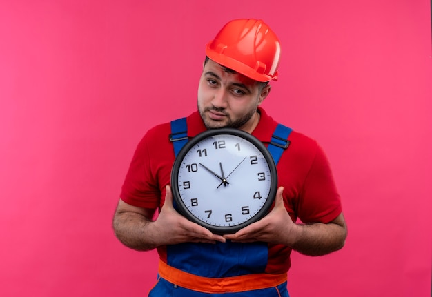 Молодой строитель в строительной форме и защитном шлеме держит настенные часы, глядя в камеру с несчастным лицом