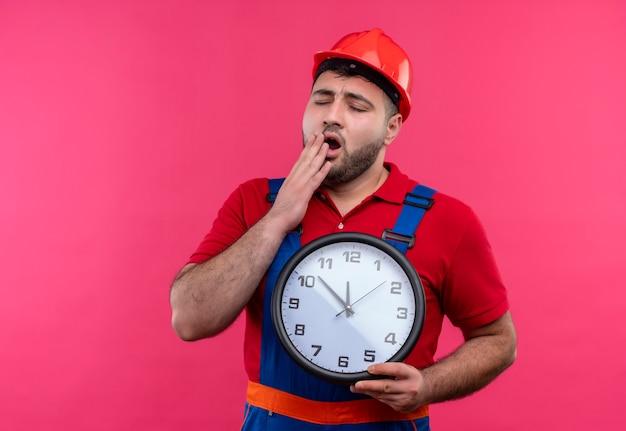 Молодой строитель в строительной форме и защитном шлеме, держащий настенные часы, зевая, усталый