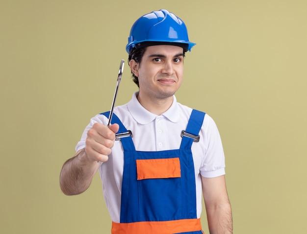 Молодой строитель в строительной форме и защитном шлеме, держащий гаечный ключ, глядя на переднюю улыбку, стоя над зеленой стеной