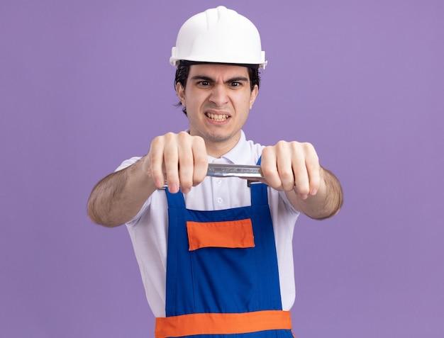 紫色の壁の上に立っている怒った顔でそれを見てレンチを保持している建設制服と安全ヘルメットの若いビルダー男