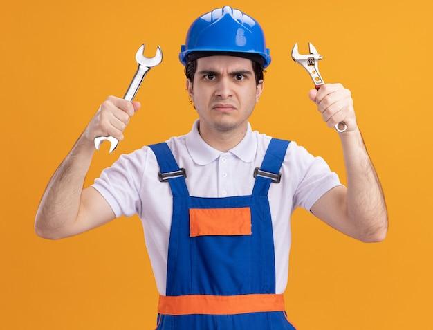 オレンジ色の壁の上に立っている怒っている顔で正面を見てレンチを保持している建設制服と安全ヘルメットの若いビルダー男