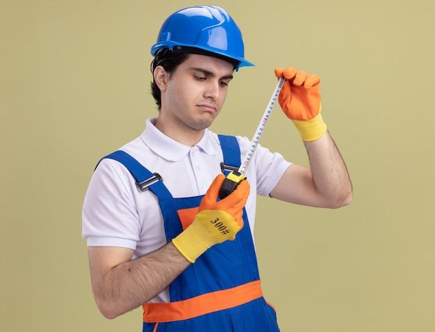 Молодой строитель в строительной форме и защитном шлеме в резиновых перчатках держит рулетку, глядя на нее с серьезным лицом, стоящим над зеленой стеной