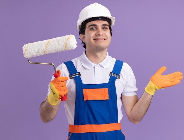 紫色の壁の上に立っている顔に笑顔で脇を見てペイントローラーを保持しているゴム手袋の建設制服と安全ヘルメットの若いビルダー男